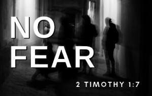 """A distorted picture of people in the shadows with the words """"No fear"""" in the foreground."""